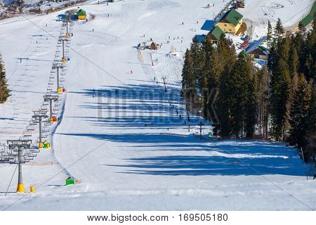 Chairs on chairlift ropeway in winter mountains