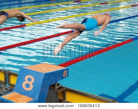 swimming competition, two swimmers were jumping from starting point into swimming pool, swimmers floating in the air