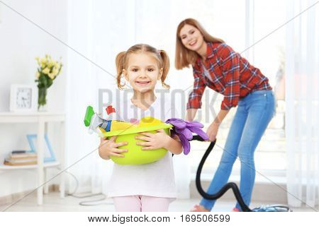 Little girl and her mother doing cleanup at home
