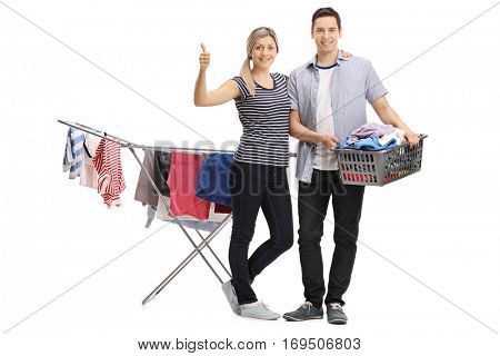 Full length portrait of a woman giving a thumb up with a guy holding a laundry basket in front of a rack dryer isolated on white background
