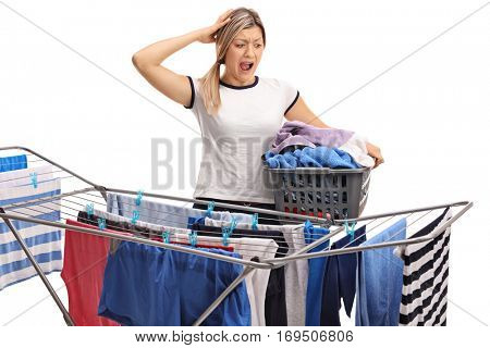 Woman with a laundry basket holding her head in disbelief and looking at a clothing rack dryer isolated on white background