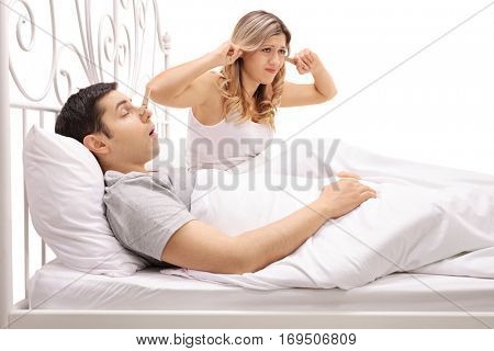 Man sleeping and snoring next to a woman plugging her ears isolated on white background