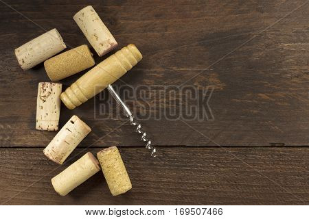 A photo of an old-fashioned corkscrew with a corks, shot from above on a dark wooden background texture with plenty of copy space. A design template for a wine list or a tasting invitation