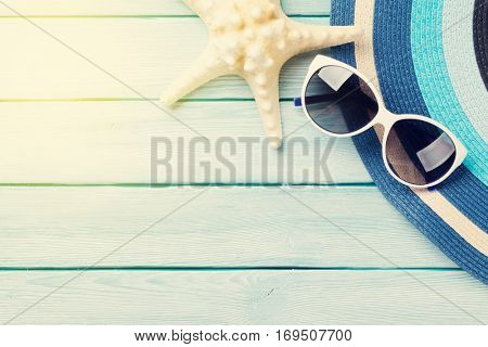 Beach accessories. Hat, sunglasses and starfish on wooden background. Top view with copy space. Sunny toned