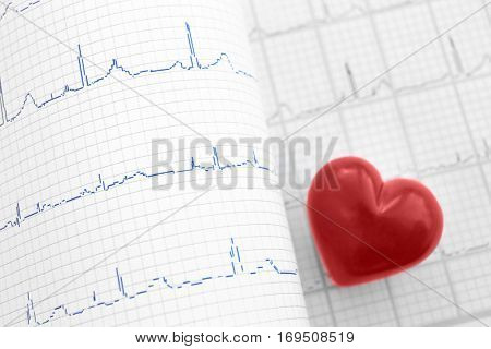 Electrocardiogram in paper form and red heart, closeup