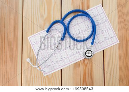 Electrocardiogram in paper form and stethoscope on wooden table