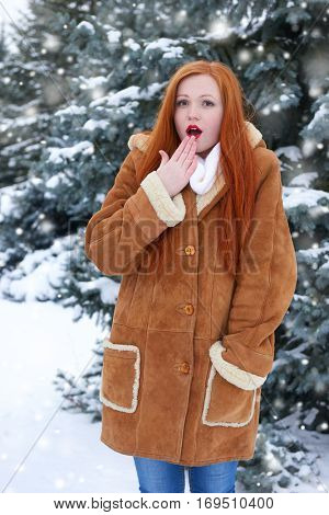 beautiful woman on winter outdoor, snowy fir trees in forest, long red hair, wearing a sheepskin coat