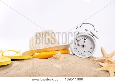 White vintage alarm clock beach slippers straw hat suntan lotion and starfish on the sand on a white background