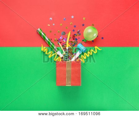 Red gift box with various party confetti balloons streamers noisemakers and decoration on a multicolored background. Colorful celebration background. Flat lay