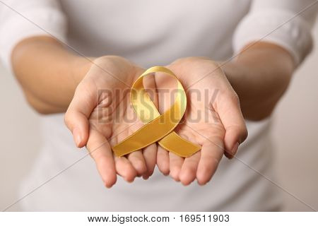 Close up view of female hands holding golden ribbon. Children cancer concept