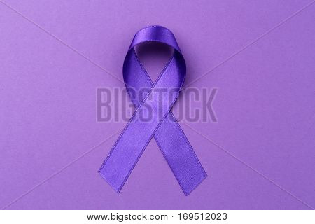 Violet ribbon on color background. Family violence, Alzheimer disease and pancreas cancer concept