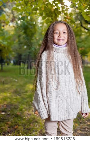 Beautiful little girl in white sweater posing in autumn Park near the tree