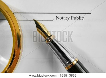 Notary public document, magnifier and fountain pen, close up view
