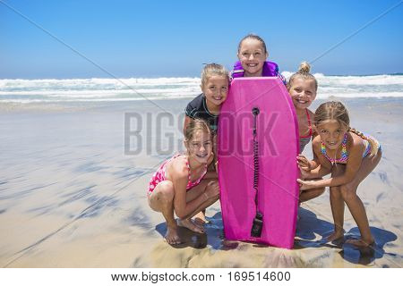 Cute group of kids standing by a boogie boards at the beach while playing in the ocean on vacation. Lots of copy space.