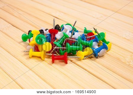 heap of multi color push pins on a wooden board.