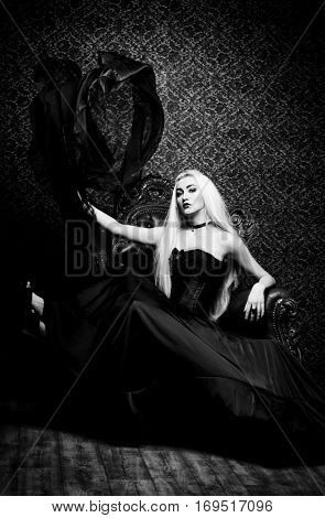 Gothic style. Black-and-white portrait of a beautiful young woman with long blonde hair and black make-up posing in long black dress in vintage interior. Antique castle style. Halloween.