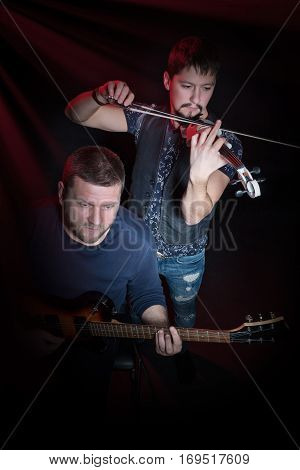 Two bearded men playing on electric guitar and electroviolin on a black background, top view