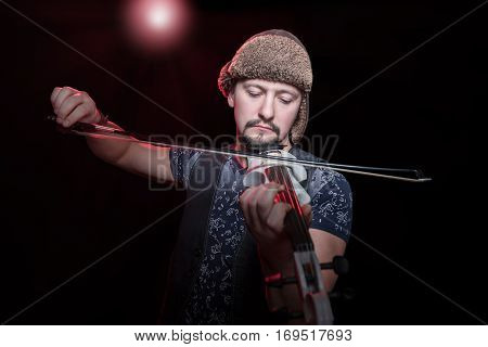 Bearded man in a funny hat with earflaps plays on a white electric violin, with a red backlighting on black background
