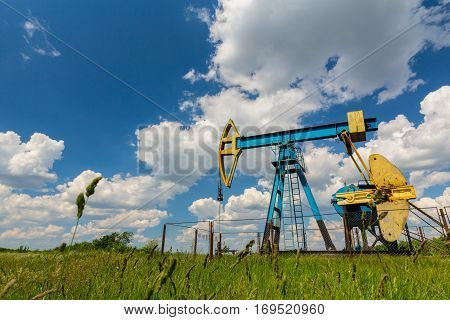 Oil field with pump jack, profiled on blue sky with white clouds, on a sunny day in spring