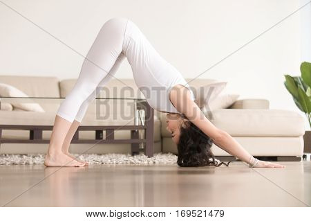 Young attractive woman practicing yoga at home, standing in Downward facing dog exercise, adho mukha svanasana pose, working out, wearing white clothes, indoor full length, living room