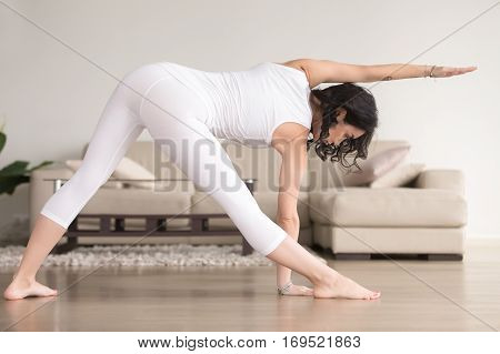 Young attractive woman practicing yoga at home, standing in extended triangle exercise, Utthita Trikonasana pose, working out, wearing white clothes, indoor full length, living room. Back view