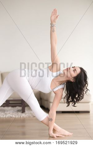Young attractive woman practicing yoga at home, standing in Revolved Triangle exercise, Parivrtta Trikonasana pose, working out, wearing white clothes, indoor, living room