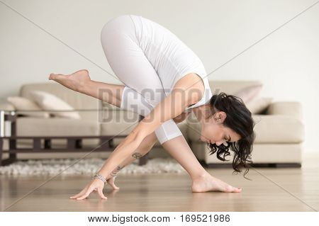 Side view portrait of young sporty cool attractive woman practicing fitness at home, doing yoga pose, balance exercise, dancing, working out, wearing white clothes, indoor full length, living room