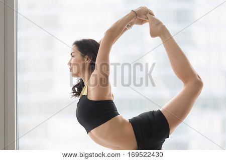 Portrait of young attractive woman practicing yoga, doing Natarajasana exercise, Lord of the Dance pose, working out wearing sportswear, black tank top, shorts, indoor, floor window with city, closeup