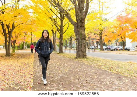 Woman walking at outdoor with gingko tree plant