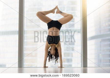 Young modern dancer attractive woman practicing, doing handstand exercise, dance pose, working out, wearing sportswear, black tank top, shorts, indoor full length, against floor window with city view