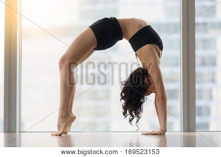 Young attractive woman practicing yoga, standing in Urdhva Dhanurasana exercise, Bridge pose, working out, wearing sportswear, black tank top, shorts, indoor full length, floor window with city view