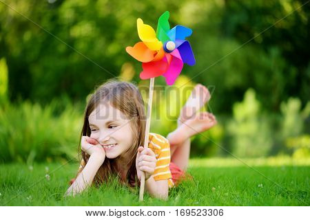 Adorable Little Girl Holding Colorful Toy Pinwheel On Summer Day
