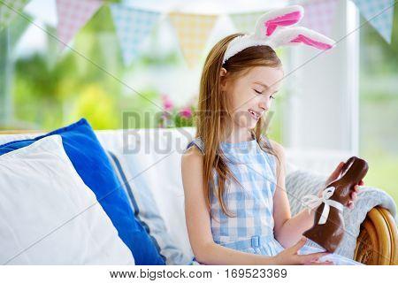 Cute Little Girl Wearing Bunny Ears Eating Chocolate Easter Rabbit