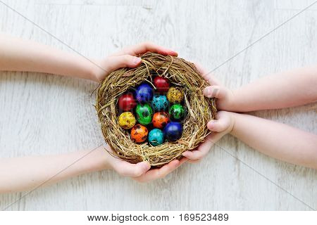 Two Children Holding A Nest With Colored Easter Eggs At Home On Easter Day