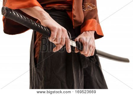 Man in chinese traditional red costume with dragon print holding sword in scabbard close up shot in studio