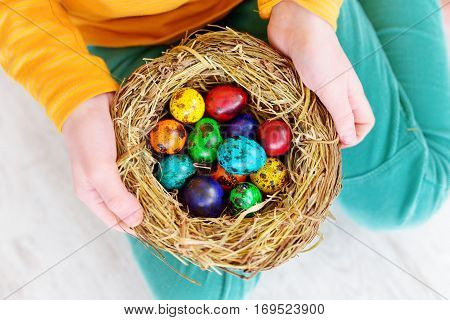 Cute Little Girl Holding A Nest With Colored Easter Eggs At Home On Easter Day. Celebrating Easter A