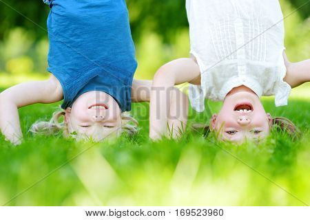 Happy Children Playing Head Over Heels On Green Grass