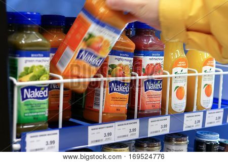 Coquitlam, BC, Canada - December 30, 2016 : Woman picking Naked mighty mango juice inside London drugs store