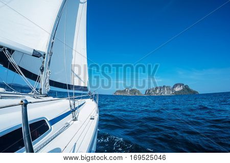 Sailing vessel moves in a sea under the sails towards the island