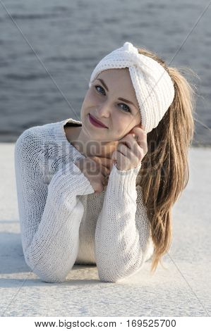 Young attractive woman wearing white knitted sweater and ear warmer turban. Lovely smile