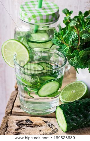 Glass jar mug with cleansing cucumber water with lime and mint ingredients agua fresca spring outdoors