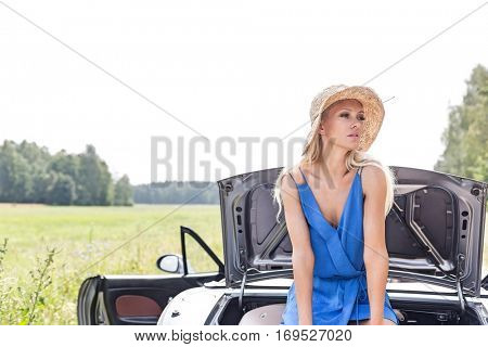 Woman looking away while sitting on convertible trunk against clear sky