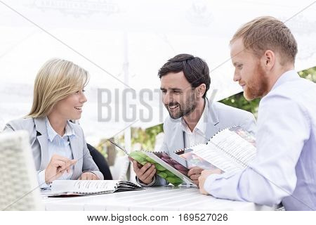 Happy businesspeople reading menu at sidewalk cafe
