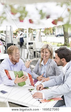 Portrait of happy businesswoman with male colleagues deciding menu at sidewalk cafe