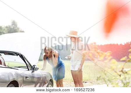 Friends repairing broken down car on sunny day