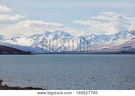 Snowy mountain peaks line the shore of Lake Tekapo in the South Island of New Zealand.Lake Tekapo is the second-largest of three roughly parallel lakes in the South Island of New Zealand.