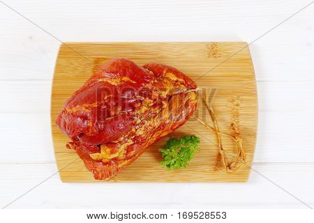 chunk of smoked pork meat on wooden cutting board