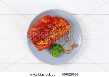 chunk of smoked pork meat on blue plate