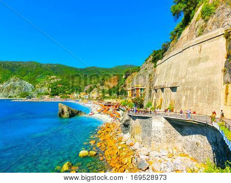 Monterosso, Italy - People on the coastline of Monterosso in Italy. Monterosso is one of five famous coastline villages in the Cinque Terre National Park.