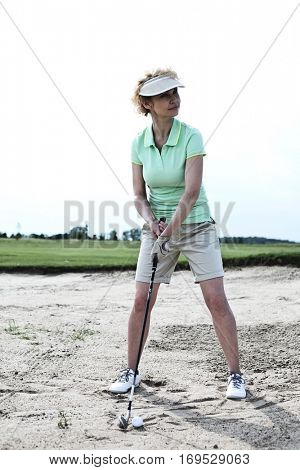 Woman playing golf at course against clear sky